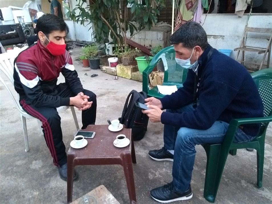 مواطن عالم يجري مقابلة وجاهية مع أحد شكان حي الكرنتينا ضمن مساحة مفتوحة (تصوير: علي غدار)